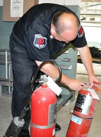 Fire Fighter Checking Gauges on Fire Extinguishers
